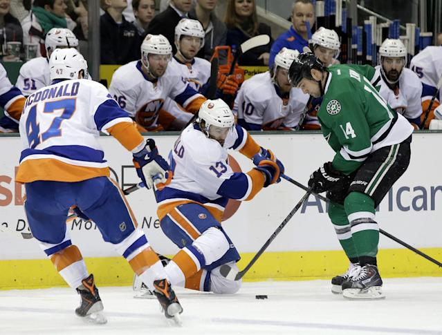 New York Islanders' Andrew MacDonald (47) watches as right wing Colin McDonald (13) compete for control of the puck against Dallas Stars' Jamie Benn (14) in the first period of an NHL hockey game, Sunday, Jan. 12, 2014, in Dallas. (AP Photo/Tony Gutierrez)