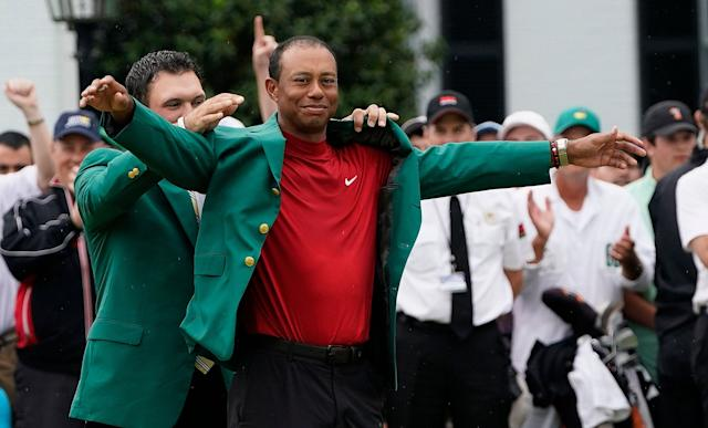 Patrick Reed helps Tiger Woods with his green jacket after Woods won the Masters golf tournament Sunday, April 14, 2019, in Augusta, Ga. (AP)