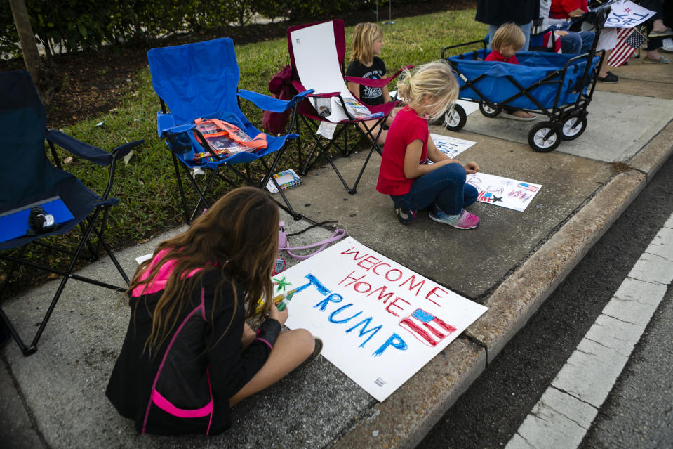 US President Donald Trump supporters paint signs as they wait for the motorcade to pass by on their way to Mar-a-Lago in Palm Beach, Florida, on January 20, 2021. (Photo by Eva Marie UZCATEGUI / AFP) (Photo by EVA MARIE UZCATEGUI/AFP via Getty Images)