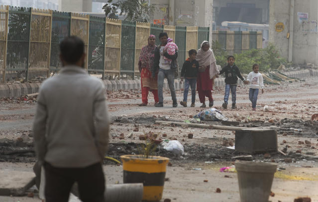 A family walks past a road littered with stones after Tuesday's violence in New Delhi, India, Wednesday, Feb. 26, 2020. At least 20 people were killed in three days of clashes in New Delhi, with the death toll expected to rise as hospitals were overflowed with dozens of injured people, authorities said Wednesday. The clashes between Hindu mobs and Muslims protesting a contentious new citizenship law that fast-tracks naturalization for foreign-born religious minorities of all major faiths in South Asia except Islam escalated Tuesday. (AP Photo/Rajesh Kumar Singh)