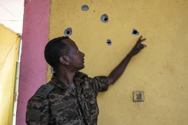 Impact: An Ethiopian soldier points to bullet holes left after the attack on the base in Dansha