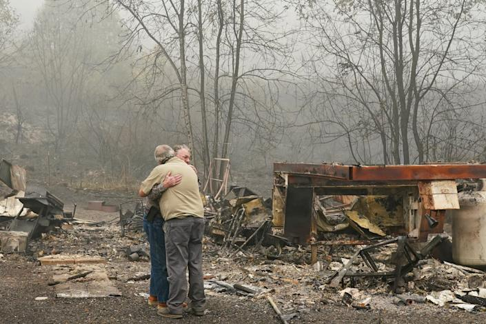 Larry Weyand (L) hugs Darwin Seim in front of Weyand's burned mobile home at the Clackamas River RV Park on September 14, 2020 in Estacada, Oregon.