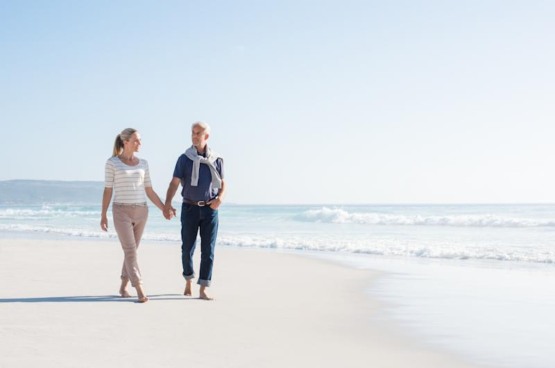 An older man and woman take a walk on the beach.