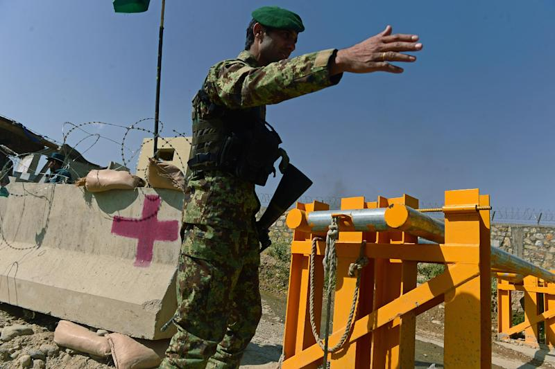 An Afghan National Army soldier gestures outside the gates of a British-run military academy outside Kabul, on August 5, 2014, where a man in Afghan military uniform opened fire on NATO troops inside the premises