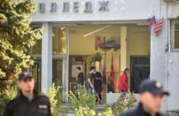 People cleaned the college entrance in Kerch, Crimea, after Wednesday's shooting rampage