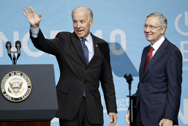Vice President Joe Biden, accompanied by Senate Majority Leader Harry Reid of Nev. waves after giving a key note speech at the National Clean Energy Summit, Tuesday, Aug. 30, 2011, in Las Vegas.  (AP Photo/Julie Jacobson)