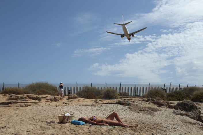 FILE - In this Wednesday, July 29, 2020 file photo, a woman sunbathes on the beach as an airplane lands at the Balearic Islands capital of Palma de Mallorca, Spain. Faced with a possible flood of visitors from Germany later this month, authorities in Spain's Balearic Islands are warning hotel owners that tourists must adhere to coronavirus restrictions the same way residents do. The archipelago in the Mediterranean Sea is strengthening measures to combat the virus before the Easter period. But the restrictions haven't stopped eager German tourists who have rushed to book flights and accommodation this week following their government's removal of the islands from a list of high-risk contagion zones. (AP Photo/Joan Mateu, File)