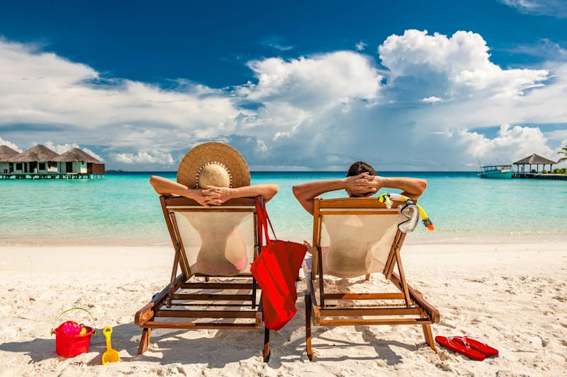 A man and woman relaxing in beach chairs on a tropical beach.