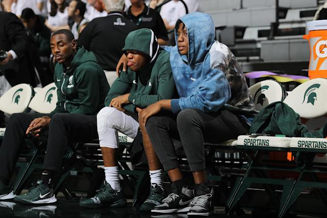 """<a class=""""link rapid-noclick-resp"""" href=""""/ncaab/players/137368/"""" data-ylk=""""slk:Cassius Winston"""">Cassius Winston</a> (middle) and his brother Khy Winston (right) watch warm ups prior to the game against the <a class=""""link rapid-noclick-resp"""" href=""""/ncaaw/teams/binghamton/"""" data-ylk=""""slk:Binghamton Bearcats"""">Binghamton Bearcats</a>. (Photo by Rey Del Rio/Getty Images)"""