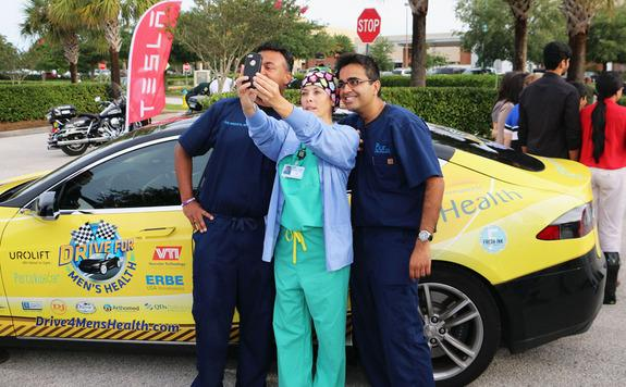 Doctors pause for a selfie with a nurse during the 2014 Drive for Men's Health. For this year's drive, Dr. Jamin Brahmbhatt and Dr. Sijo Parekattil, co-directors of the PUR Clinic in Clermont, Fl., will drive an all-electric Tesla more than 6,0