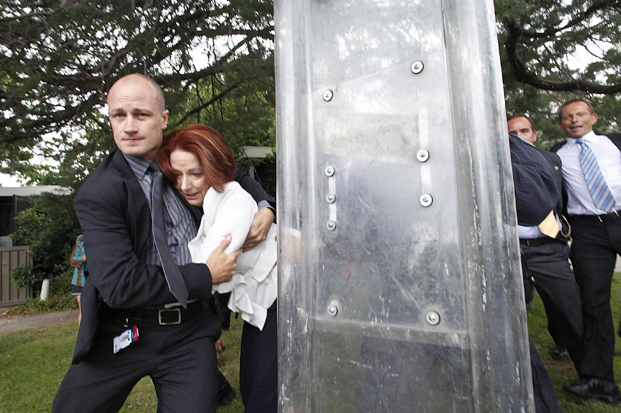 Prime Minister Julia Gillard, second from left, is escorted out for safety by body guards and police through a crowd of rowdy protesters following a ceremony to mark Australia's national day in Canberra, Australia, Thursday Jan. 26, 2012. Some 200 supporters of indigenous rights surrounded a Canberra restaurant and banged its windows on Thursday while Gillard and opposition leader Tony Abbott were inside officiating at an award ceremony. (AP Photo/Lukas Coch) AUSTRALIA OUT