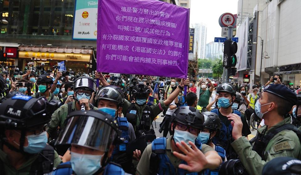 Police officers display a purple flag warning anti-government protesters in Causeway Bay on October 1 that they may be violating the city's controversial national security law. Photo: Sam Tsang