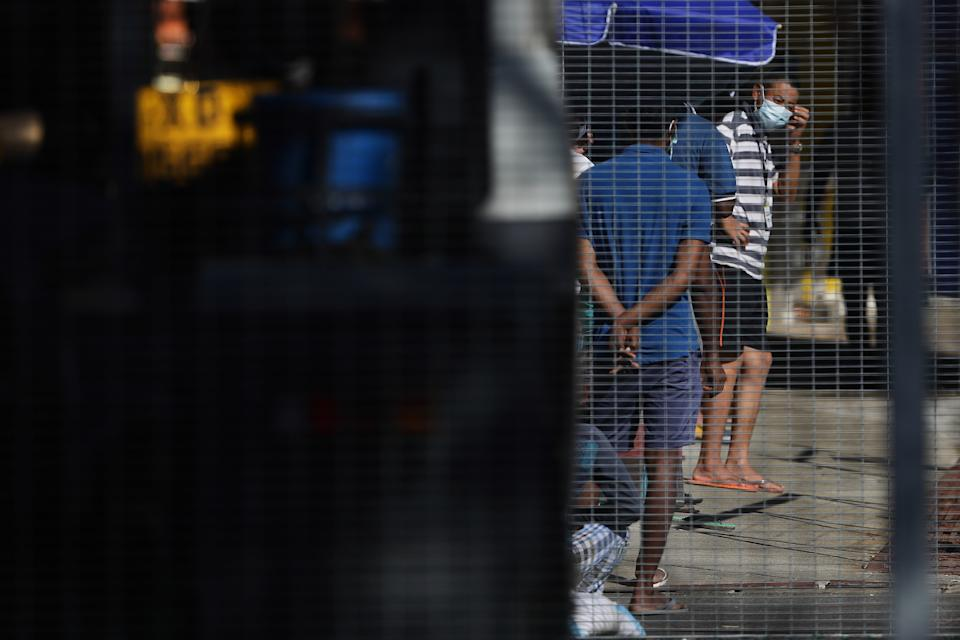 SINGAPORE - APRIL 21:  Foreign workers are seen in the compound of a dormitory on April 21, 2020 in Singapore. Singapore is now battling to control a huge outbreak in the coronavirus (COVID-19) local transmission cases among the migrant workers as it recorded a daily high of 1426 new COVID-19 cases on April 20, bringing the country's total to 8014.  (Photo by Suhaimi Abdullah/Getty Images)