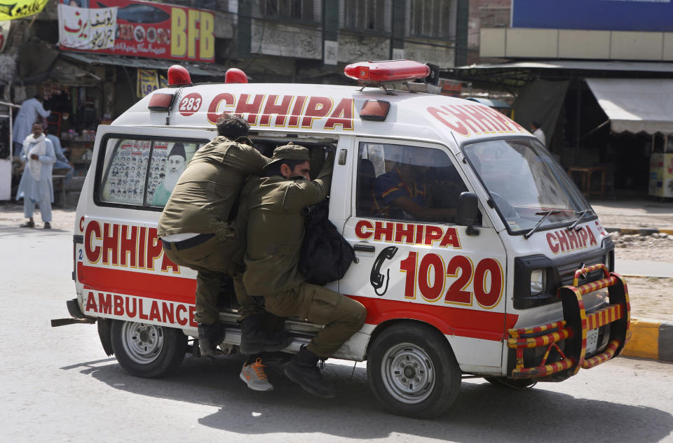 Police officers hang on to an ambulance carrying their colleagues that were injured during a clash with supporters of Tehreek-e-Labiak Pakistan, a banned Islamist party, protesting the arrest of their party leader Saad Rizvi, in Lahore, Pakistan, Sunday, April 18, 2021. A crackdown by security forces on protesting supporters of the banned party left several people dead and many others, including police officers, injured, a police spokesman said Sunday. (AP Photo/K.M. Chaudary)