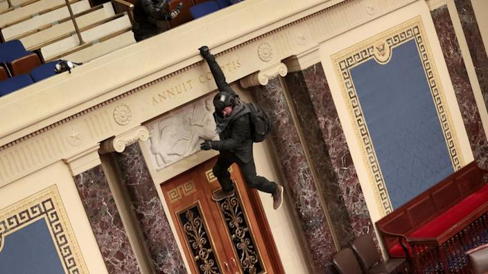 A protester hangs from the wall of the US Senate chamber