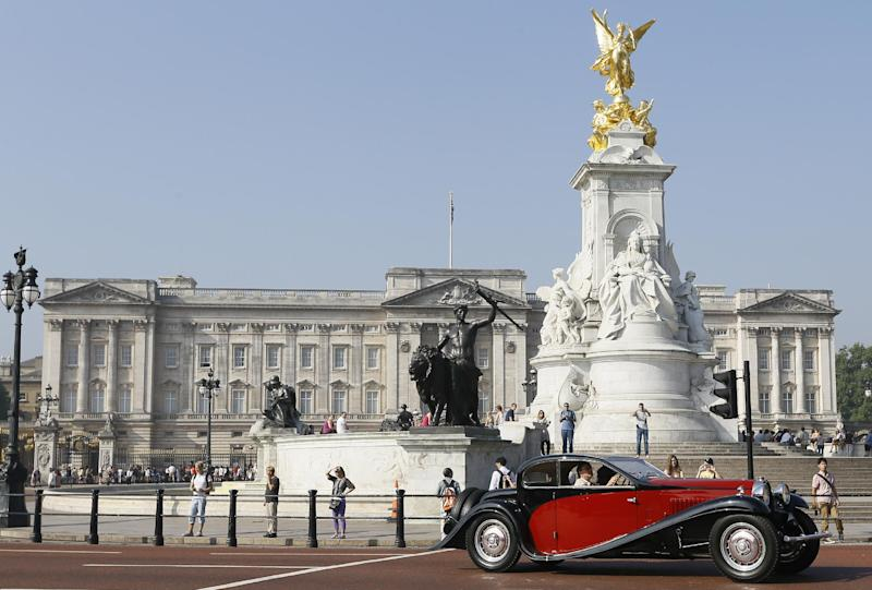 A classic car heads past Buckingham Palace on its way to the Concours of Elegance classic car event on the opening morning in London, Thursday, Sept. 5, 2013. The charity event is being held at Marlborough House where up to 60 rare historic cars are coming from around the world with a special Preview Day on Thursday and open to the public on Friday and Saturday. The 2012 event raised in excess of £250,000 ($391,000/296,000 euro) for charity. (AP Photo/Kirsty Wigglesworth)
