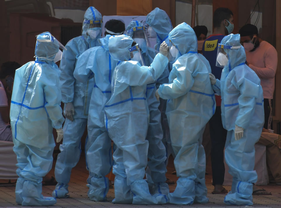 Health workers and volunteers in personal protective suits wait to receive patients outside a COVID-19 hospital that was set up at a Sikh Gurdwara in New Delhi, India, Monday, May 10, 2021. (AP Photo/Ishant Chauhan)