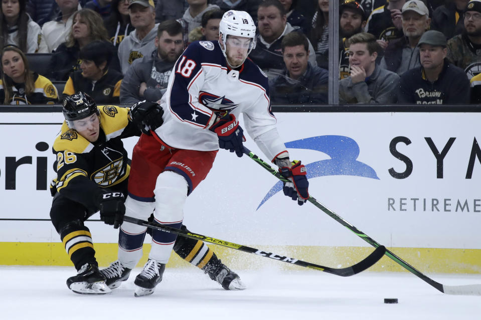 Columbus Blue Jackets center Pierre-Luc Dubois (18) controls the puck against Boston Bruins center Par Lindholm (26) in the second period of an NHL hockey game, Thursday, Jan. 2, 2020, in Boston. (AP Photo/Elise Amendola)