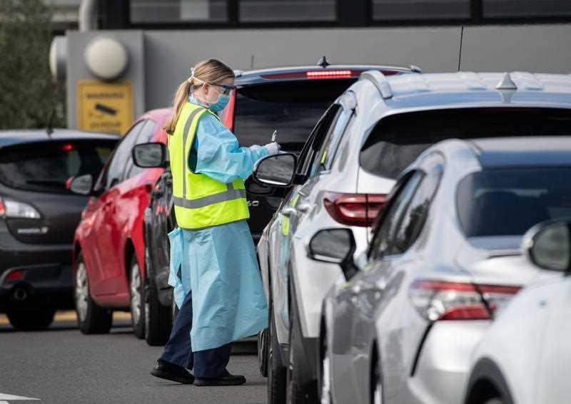 NSW Health workers dressed in Personal Protective Equipment (PPE) are seen collecting information as people wait in their cars to receive coronavirus testing at the Crossroads Hotel in Sydney.