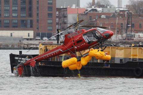 The wreckage of a chartered Liberty Helicopters helicopter that crashed into the East River is hoisted from the water in New York - Credit: REUTERS/SHANNON STAPLETON