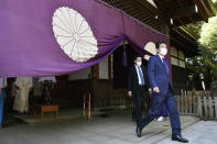 Former Japanese Prime Minister Shinzo Abe, right, leaves after praying at Yasukuni Shrine in Tokyo Wednesday, April 21, 2021, the first day of the annual Spring Rites, the shrine's biannual festival honoring the war dead, including Japanese war criminals. (Tsuyoshi Ueda/Kyodo News via AP)