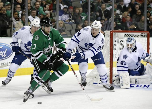 Dallas Stars center Rich Peverley (17) controls the puck , ooking for a shot opportunity, as Toronto Maple Leafs' Morgan Rielly (44) and Peter Holland (24) help goalie Jonathan Bernier (45) during the first period of an NHL hockey game, Thursday, Jan. 23, 2014, in Dallas. (AP Photo/Tony Gutierrez)