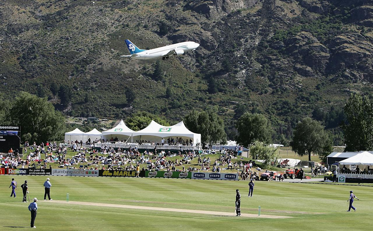 QUEENSTOWN, NEW ZEALAND - DECEMBER 31: A plane takes off from the nearby airport during the first One Day International match between New Zealand and Sri Lanka at the Queenstown Events Centre December 31, 2005 in Queenstown, New Zealand. (Photo by Phil Walter/Getty Images)