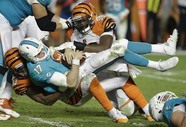 Miami Dolphins quarterback Ryan Tannehill (17) is sacked by Cincinnati Bengals defensive ends Carlos Dunlap (96) and Michael Johnson (93) during the second half of an NFL football game, Thursday, Oct. 31, 2013, in Miami Gardens, Fla. (AP Photo/Lynne Sladky)