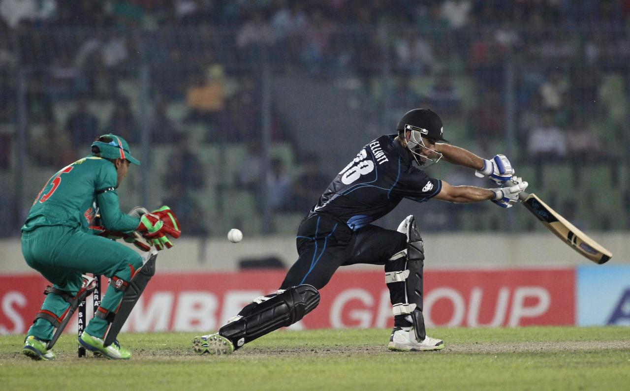 New Zealand's Grant Elliott plays a shot as Bangladesh's captain and wicket keeper Mushfiqur Rahim (L) tries to catch during their first one-day international (ODI) cricket match in Dhaka October 29, 2013. REUTERS/Andrew Biraj (BANGLADESH - Tags: SPORT CRICKET)
