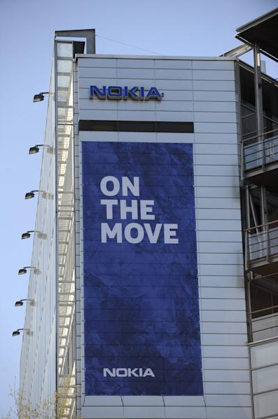 """The Nokia headquarters building in Keilaniemi, Espoo, Finland, displays a banner saying they are moving Friday April 25, 2014. Nokia headquarters are """"On the move"""" to join Nokia Solutions and Networks' headquarters in Karakallio, Espoo. Nokia said Friday it has completed the 5.44 billion-euro ($7.5 billion) sale of its troubled cellphone and services division to Microsoft Corp., ending a chapter in the former world leading cellphone maker's history that began with paper making in 1865. The closure of the deal, which includes a license to a portfolio of Nokia patents to Microsoft Corp., follows delays in global regulatory approvals, and ends the production of mobile phones by the Finnish company, which had led the field for more than a decade, peaking with a 40-percent global market share in 2008. (AP Photo/Lehtikuva, Mikko Stig) FINLAND OUT"""