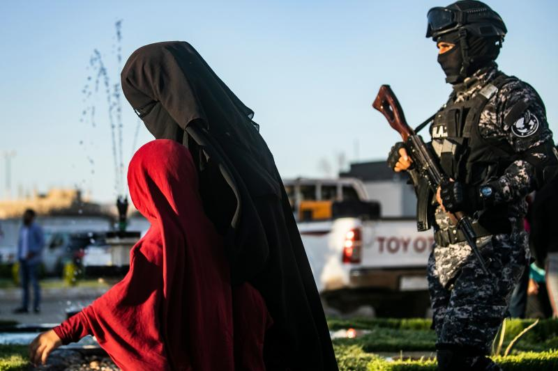 "US-backed Syrian Democratic Forces (SDF) escort a fully veiled woman and a child in the northern Kuridish-Syrian city of Qamishli as Uzbek women and children linked to the Islamic State group are handed over to diplomats from the Central Asian country for repatriation, on May 29, 2019. - In total more than 300 Uzbeks were due to be sent home, spokesman Kamal Akef told AFP, as the Kurds look to transfer away thousands of foreign jihadists trapped in camps following the defeat of the IS ""caliphate"" by US-backed forces. Hundreds of Uzbeks are believed to have joined militants fighting in Iraq and Syria including IS. (Photo by Delil souleiman / AFP) (Photo credit should read DELIL SOULEIMAN/AFP/Getty Images)"