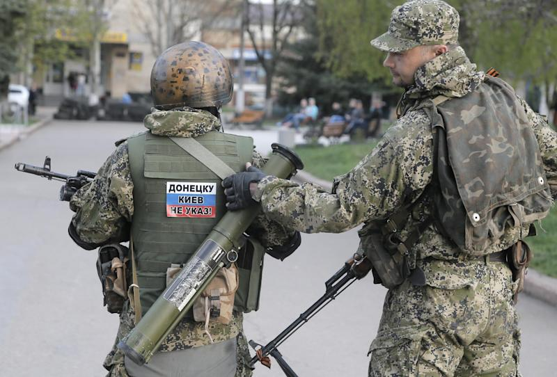 Pro-Russian gunman patrol a streets in downtown Slovyansk, Eastern Ukraine, Friday, April 18, 2014. Pro-Russian insurgents defiantly refused Friday to surrender their weapons or give up government buildings in eastern Ukraine, despite a diplomatic accord reached in Geneva and overtures from the government in Kiev. (AP Photo/Efrem Lukatsky)