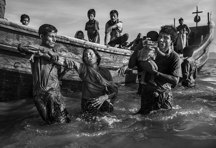 <p>Rohingya refugees flee into Bangladesh: A Rohingya refugee is helped from a boat as she arrives at Shah Porir Dwip, near Cox'€™s Bazar, Bangladesh, Oct. 1, 2017.<br>Attacks on the villages of Rohingya Muslims in Myanmar, and the burning of their homes, led to hundreds of thousands of refugees fleeing into Bangladesh on foot or by boat. Many died in the attempt. According to UNICEF, more than half of those fleeing were children. In Bangladesh, refugees were housed in existing camps and makeshift settlements. Conditions became critical; basic services came under severe pressure and, according to a Médecins Sans Frontières physician based there, most people lacked clean water, shelter and sanitation, bringing the threat of disease. (Photo: Kevin Frayer/Getty Images) </p>