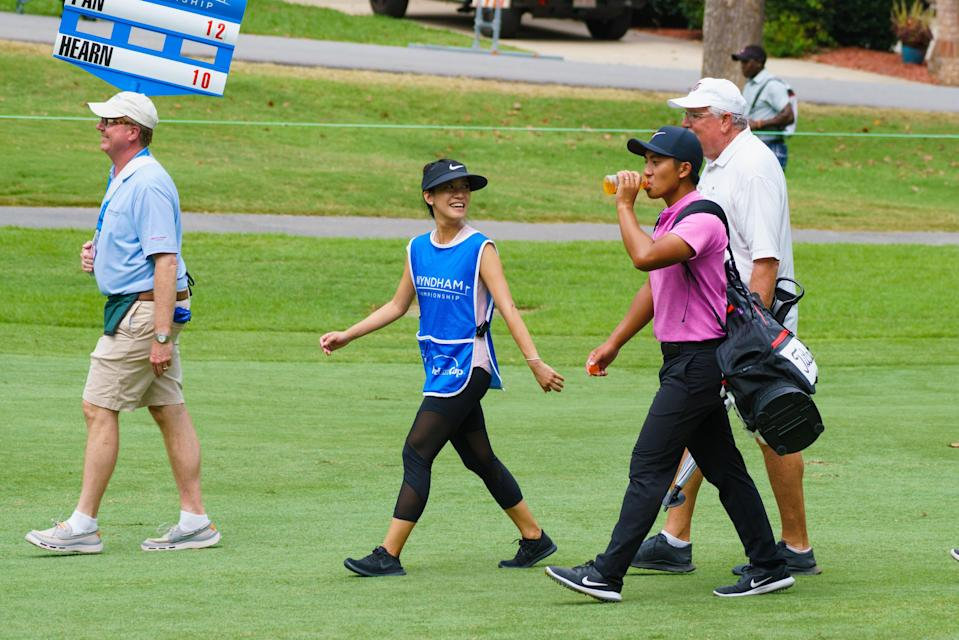 GREENSBORO, NC - AUGUST 18: C.T. Pan carries his own clubs while giving his wife Michelle Lin a break as play is suspended during the third round of the Wyndham Championship on August 18, 2018, at Sedgefield Country Club in Greensboro, NC. (Photo by Jeremy McKnight/Icon Sportswire via Getty Images)
