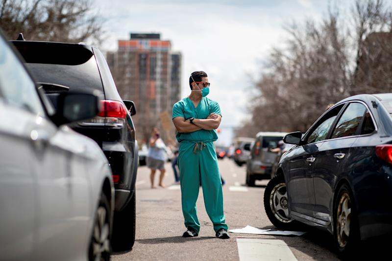 Image: A health care worker stands in the street while protesters demand stay-at-home orders be lifted outside of the State Capitol in Denver on April 19, 2020. (Alyson McClaran / Reuters)