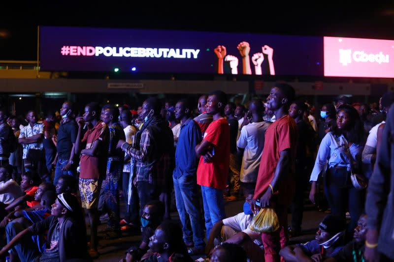 "Demonstrators gather beside an electronic billboard displaying the slogan ""End police brutality"", during a protest in Lagos"