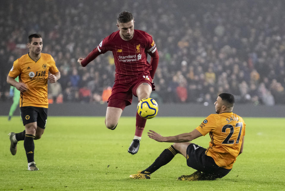 Liverpool's Jordan Henderson (centre) competing with Wolverhampton Wanderers' Romain Saiss during their Premier League match.