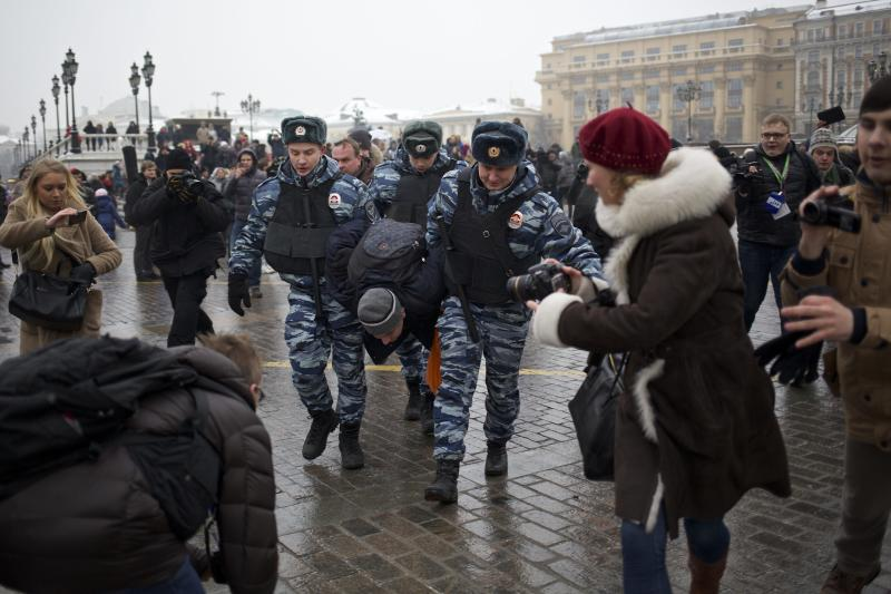 "FILE - In this Saturday, Feb. 8, 2014 file photo, police officers detain a protester near Red Square during an unauthorized protest in Moscow, Russia. Around 40 people gathered in downtown Moscow to protest the decision of leading Russian cable and satellite companies to drop the channel, Dozhd (TV Rain). The independent television station Dozhd, or TV Rain, came under attack after asking viewers in January whether the Soviet Union should have surrendered Leningrad, now St. Petersburg, to save the lives of the 1 million people who died during the nearly 900-day Nazi siege of the city during the war. The station quickly pulled the poll and apologized, but President Vladimir Putin's spokesman said the station had crossed a ""red line."" Russian cable operators lined up to drop Dozhd from their packages and prosecutors opened an investigation. (AP Photo/Alexander Zemlianichenko, file)"