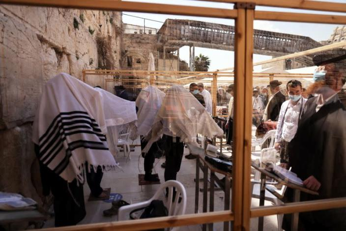 Ultra-Orthodox Jewish men, some covered in prayer shawls, are seen through a part of a partitioned area, placed for worshippers to adhere to COVID-19 restrictions, as they pray in front of the Western Wall, in Jerusalem's Old City