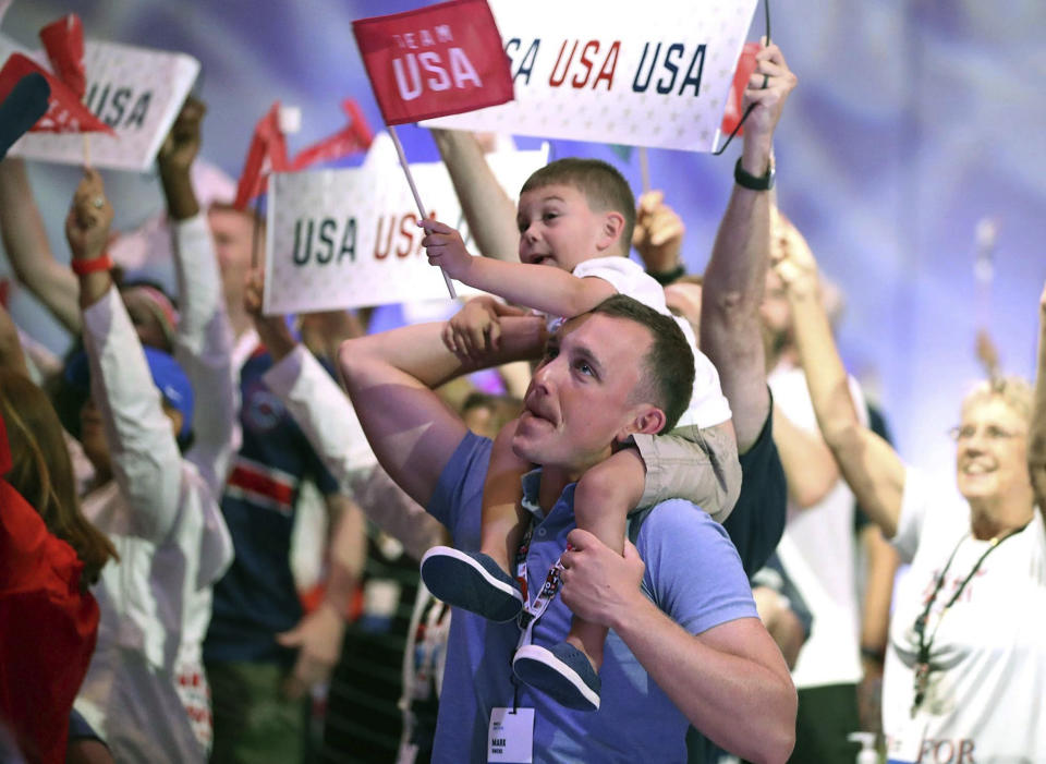 Family and friends of Olympic athletes watch the televised Olympics action live at the Olympic Family & Friends Experience at the Loews Sapphire Falls Resort at Universal Orlando in Orlando, Fla., Friday, July 30, 2021. Parents, siblings, friends and former teammates crowd into the ballroom at the resort daily to watch the Summer Games and bond with others in a similar situation, all of them unable to be in Tokyo to root on their loved ones competing for gold because of the coronavirus pandemic. (Stephen M. Dowell/Orlando Sentinel via AP)
