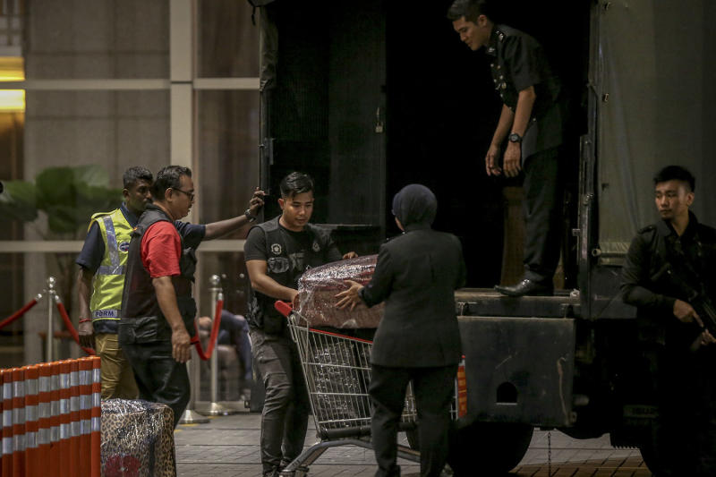 Police personnel lift suitcases filled with cash and jewellery onto a waiting Black Maria outside the Pavilion Residences, May 17, 2018. — Picture by Hari Anggara