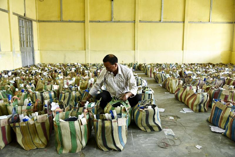 An Indian election official in the northeastern state of Assam arranges bags filled with voting materials ahead of the third phase of the country's massive general election (AFP Photo/David TALUKDAR)