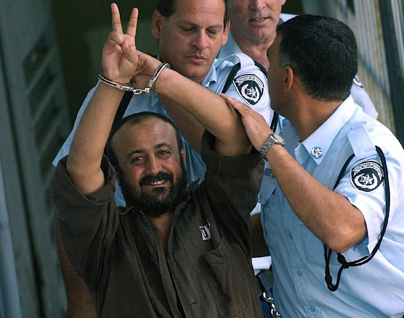 The leader of hundreds of Palestinian hunger strikers in Israeli jails, Marwan Barghouti, who has received his first Red Cross visit since the strike began, flashes the victory sign after a court hearing in 2003