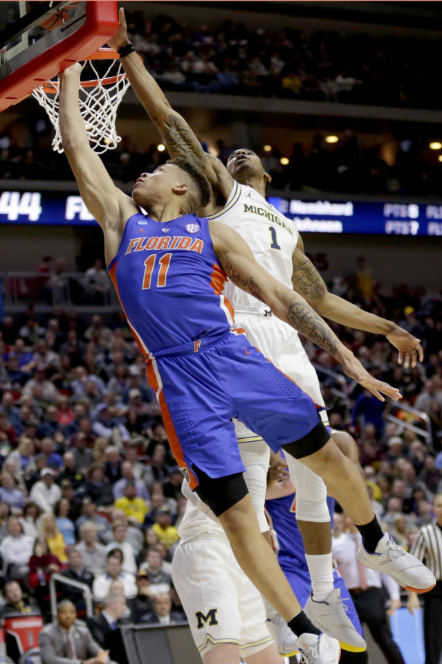 Michigan's Charles Matthews (1) blocks a layup by Florida's Keyontae Johnson (11) during the second half of a second round men's college basketball game in the NCAA Tournament, in Des Moines, Iowa, Saturday, March 23, 2019. (AP Photo/Nati Harnik)