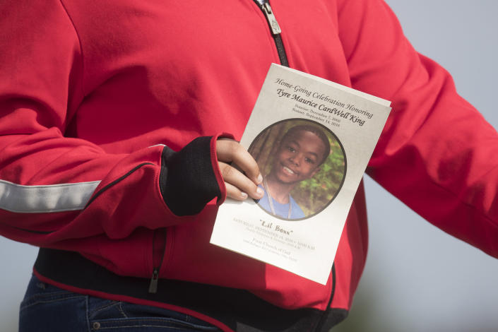 FILE - In this Sept. 24, 2016, file photo, a funeral service card bearing the likeness of Tyre King is carried by a mourner in Columbus, Ohio. The white Ohio police officer who killed 13-year-old King argued in a federal court filing Wednesday, Feb. 17, 2021, that he used reasonable force and race wasn't a factor in the shooting of the Black teenager. Columbus Officer Bryan Mason shot Tyre in 2016 while responding to a reported armed robbery. (AP Photo/John Minchillo, File)