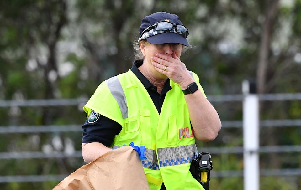 A teary Queensland Police Officer is seen investigating the scene where 53-year-old  Senior Constable David Masters was killed. Source: AAP