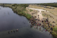 FILE - In this Sept. 21, 2021, file photo, migrants, many from Haiti, are seen wading between the U.S. and Mexico on the Rio Grande, in Del Rio, Texas. The Border Patrol's treatment of Haitian migrants, they say, is just the latest in a long history of discriminatory U.S. policies and of indignities faced by Black people, sparking new anger among Haitian Americans, Black immigrant advocates and civil rights leaders.(AP Photo/Julio Cortez, File)