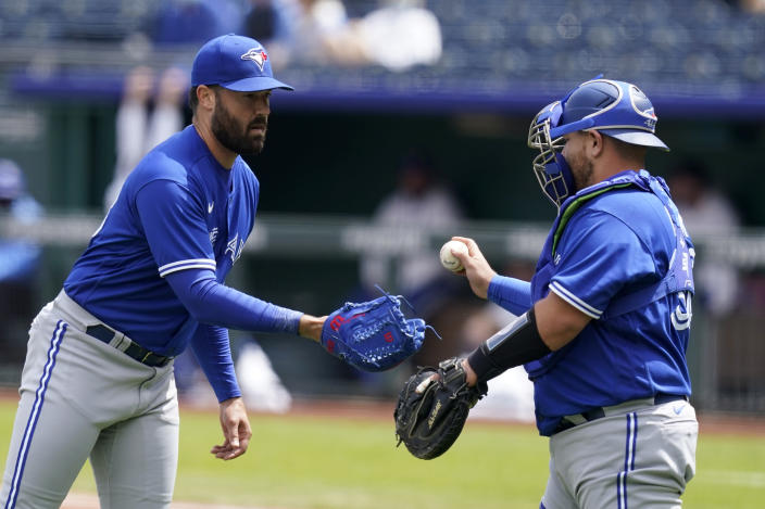 Toronto Blue Jays starting pitcher Robbie Ray, left, takes the ball from catcher Alejandro Kirk, right, after loading the bases in the first inning of a baseball game against the Kansas City Royals at Kauffman Stadium in Kansas City, Mo., Sunday, April 18, 2021. (AP Photo/Orlin Wagner)
