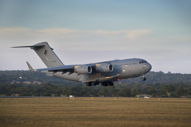 In this Friday, March 28, 2014 photo released by the Australian Defence, a Royal Australian Air Force C-17 Globemaster prepares to land at RAAF Pearce Base to help with the search for the missing Malaysia Airlines Flight 370, in Perth, Australia. Objects spotted floating in a new search area for debris from the missing Malaysian jetliner need to be recovered and inspected before they can be linked to the plane, Australian officials said Saturday. Eight planes were ready to comb the newly targeted area off the west coast of Australia after several objects were spotted Friday, including two rectangular items that were blue and gray, and ships on the scene will attempt to recover them, the Australian Maritime Safety Authority said. (AP Photo/Australian Defence, Oliver Carter)