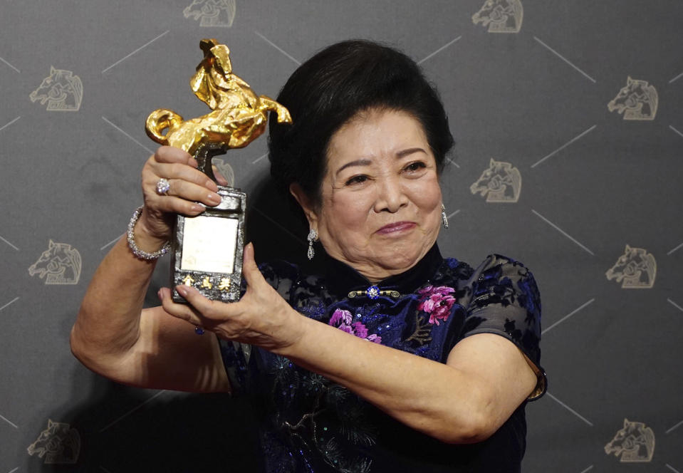 "Taiwanese actress Chen Shu-fang holds her award for Best Supporting Actress at the 57th Golden Horse Awards in Taipei, Taiwan, Saturday, Nov. 21, 2020. Chen won for the film ""Dear Tenant"" at this year's Golden Horse Awards -the Chinese-language film industry'sbiggest annual events. (AP Photo/Billy Dai)"